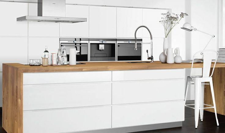 Mooie combinatie van wit en houtkleur in het keukenblok van deze Scandinavische design keuken. #scandinavischdesign #keuken