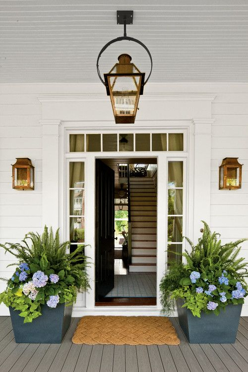 Beautiful exterior and interior entryway with lantern sconces, a framed doorway, potted flowers and a painted door | Historical Concepts
