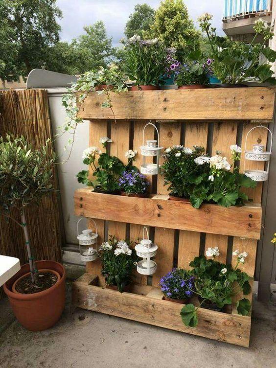 jardiniere en palette à faire soi meme, supports pour pots de fleurs et photophores blancs, plantes et fleurs, deco exterieure