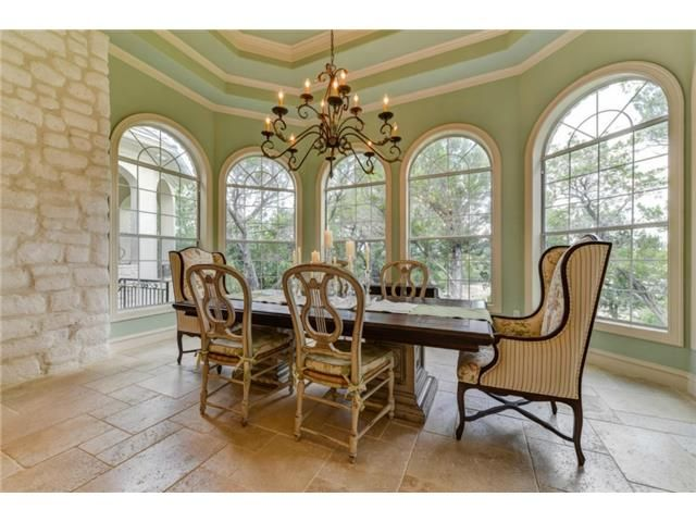 Mint green dining room with mismatched chairs at 601 S Angel Light Dr, Spicewood TX