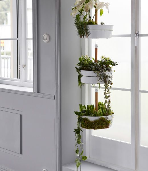 IKEA BITTERGURKA hanging planter is hung and filled with holiday plants, flowers, and moss.