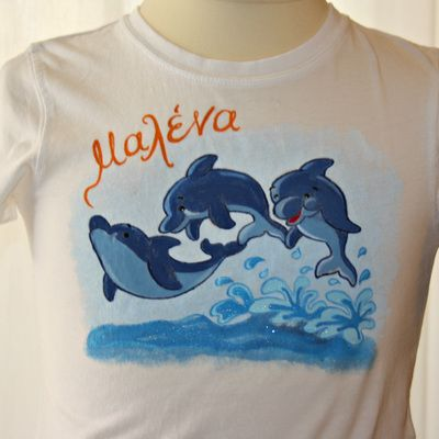 Hand painted t shirt. I use non-toxic, water based, permanent fabric colors. One more cute little tee for Malena, picturing three dolphins jumping off the water. The girl's name is written in Greek.