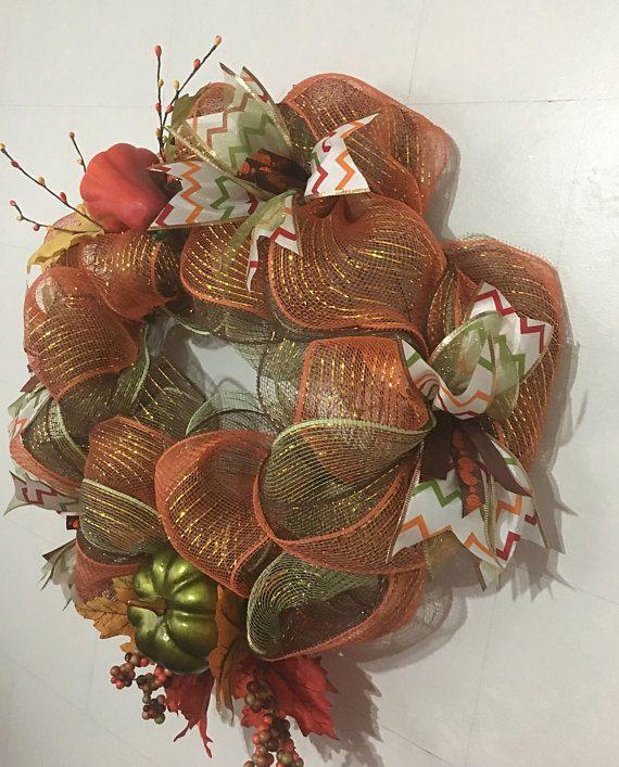 ¡Feliz otoño! Disfrute de esta corona de otoño hecha de malla de deco verde, naranja y marrón. Se acentúa con el multi coloreada cinta de diseño chevron por cable junto con la cinta de brillo verde y calabaza de 1/2 cinta. También una calabaza y calabaza con seda caen hojas. Esta