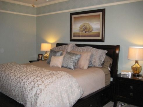 Another grey/blue bedroom with dark brown furniture.