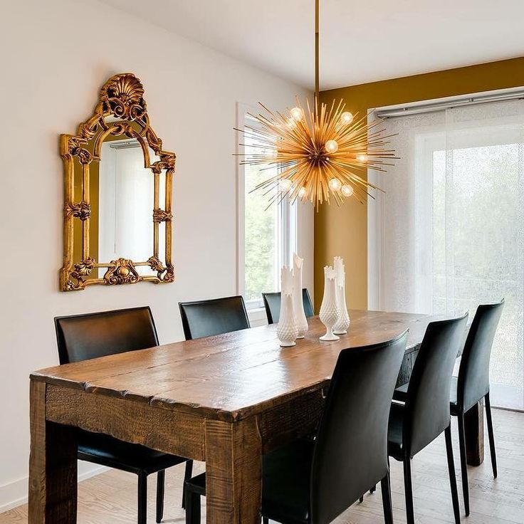 Exquisite dining room features a salvaged wood dining table lined with black leather dining chairs, Crate & Barrel Folio Viola Top-Grain Leather Dining Chairs, illuminated by a brass sea urchin chandelier.