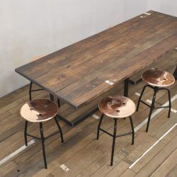 Big handcrafted industrial table, reclaimed wood top and metal legs. Loft style. Dining room. Restaurant table. Copper stools.