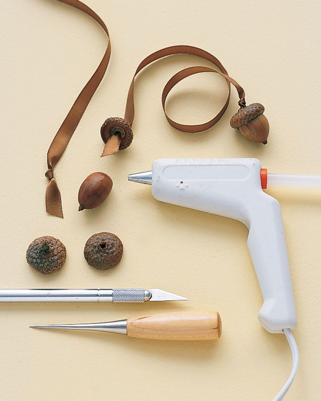 """Separate caps from the bodies of two acorns with a craft knife.  Make a small hole in each cap with an awl.  Knot one end of a 9 x 1/4"""" brown satin ribbon.  Thread other end through a cap; knot at top.  Thread through another cap; knot on both sides.  Reattach bodies."""