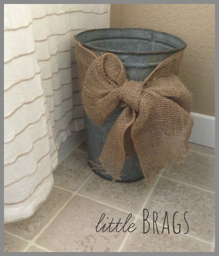 Trash can from rusty bucket or basket, wrapped with burlap ribbon