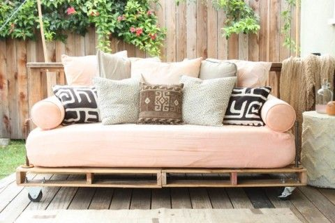 Outdoor sofa - two pallets on casters, galvanized metal pipes for the arms and back frame, and a twin size mattress and pillows for the 'cushions'.