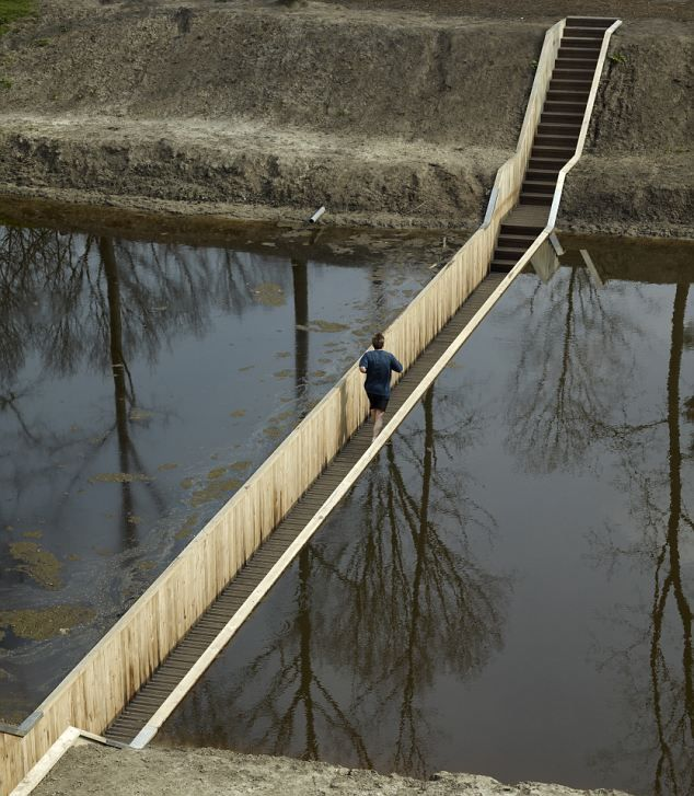 Dutch engineers build 'invisible' crossing for moat of 17th century fortress. The bridge can't be seen from a distance because the ground and the water come all the way up to its edge.