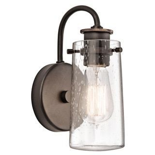 This Braelyn collection 1-light wall sconce features an olde bronze finish that will complement many urban, loft, and transitional decors. The clear seeded glass surrounding the Edison style bulb adds