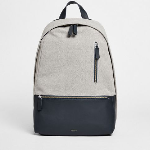 The Krøyer backpack's zip-closure interior features a padded sleeve large enough for a 15-inch laptop along with two mesh pockets and pen holders. A zippered through pocket on the back allows earbuds to extend through even when closed. The exterior also features easily accessible vertical and leather horizontal zip pockets. Where coated, the twill material is resistant to water.
