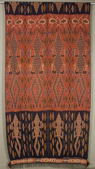 "Hinggi  Sumba. Indonesia  48""x 110""plus fringe  Warp ikat. Cotton.  The wide dark alligator border and narrow strip border at the bottom are repeated at the top. This man's shoulder cloth or sarong is probably 20 to 30 years old. It was dyed with the traditional indigo and kombu, and is in excellent condition."