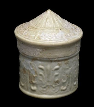 Roman white glass box with lid, 1st century A.D. Translucent white glass, mold blown, body in three part mold, cylindrical body decorated with continuous frieze of upright and inverted palmettes, on the base, four concentric circles, conical lid decorated with concentric zone of gadroons surrounded by continuous frieze of alternating upright and inverted palmettes, 7.8 cm high. Corning museum of glass