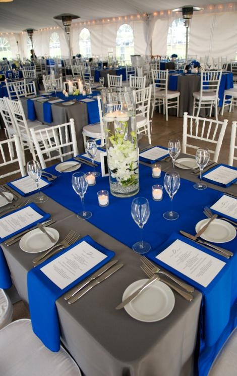 WELL PLACED: Cobalt and pewter-colored linens from EventWorks dressed the square reception tables. For centerpieces, Judy Johnston of Engaging Events submerged orchids in tall glass vases.