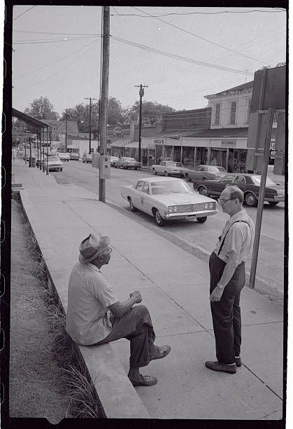 (Original Caption) This small Mississippi town has come a long way since the early 1960s when racial violence, sit-ins, marches and a Negro boycott of white merchants was the order of the day. The city's election of its first Negro mayor, Charles Evers, since Reconstruction, has done much toward bringing a changed atmosphere. Here, two elderly residents, a black and a white, chat quietly on Main Street recently. Fayette, Mississippi - Jefferson County.