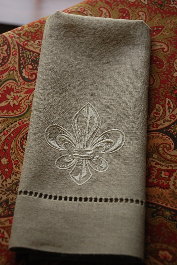 Oatmeal colored hemstitched towel with Fleur de Lis.