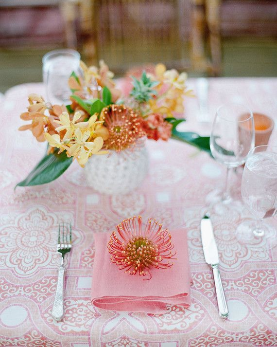 Coral pink was featured in the linens and napkins as well as the dainty pincushion protea placed on every place setting, framed by silverware from The Ark. Bolder colors were incorporated with the vibrant centerpieces of yellow and orange orchids and pincushion protea.