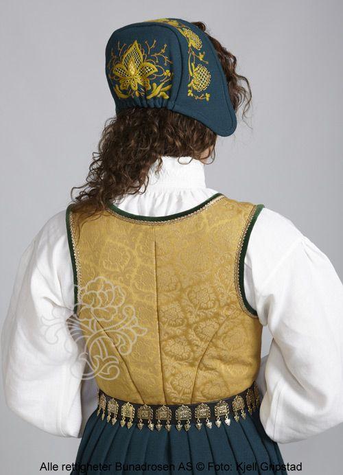Romeriksbunad L55 med sjøgrønn stakk og gyldent liv. Hovudplagg: Høglue med ein stor brodert pull eller ei hettelue med broderi.