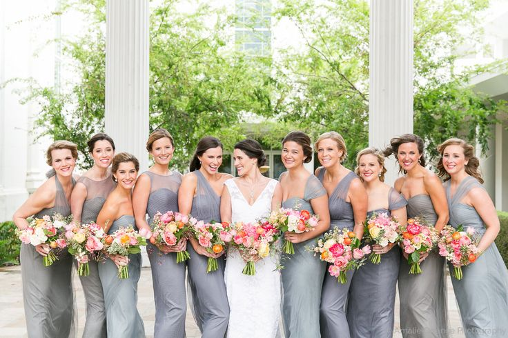bridesmaids wear shades of pale blue, grey and slate gowns and carry loose bouquets of spring flowers including coral charm peony, romantic antique garden rose, caramel antique garden rose, peach stock, pink fringe tulip, peach ranunculus, white majolik spray rose, white button chamomile, variegated italian pittosporum& jasmine vine wrapped in cream satin ribbon.