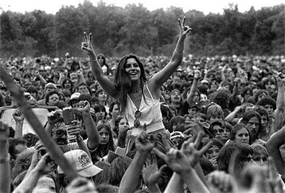 All About Peace A girl makes hand signs at the ending of a song, Woodstock, 1969.