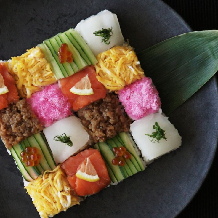 Recipe with video instructions: How to make a Mosaic Block Sushi. Ingredients: 280 cc rice, 260 cc water, 4 tsp sake, (sushi rice seasonings), 40 cc rice vinegar, 2 tsp sugar, 1 tsp salt, (sushi fillings and toppings), 3 sheets nori, cut in half, 2 slices smoked salmon, 3 thinly sliced lemon, 1/2 cucumber, thinly sliced, ikura (salmon roe), sakura denbu (pink fish flakes), 1 small fillet of squid (sashimi quality), 1 pirella leaf, cut into thin strips, (seasoned ground chicken), vegetable…
