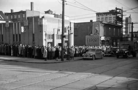 """Crowd lined up in front of a Government Liquor store on Davie Street, December 1942. (Photo by Jack Lindsay for the """"Vancouver News-Herald,"""" via Vancouver Archives)"""