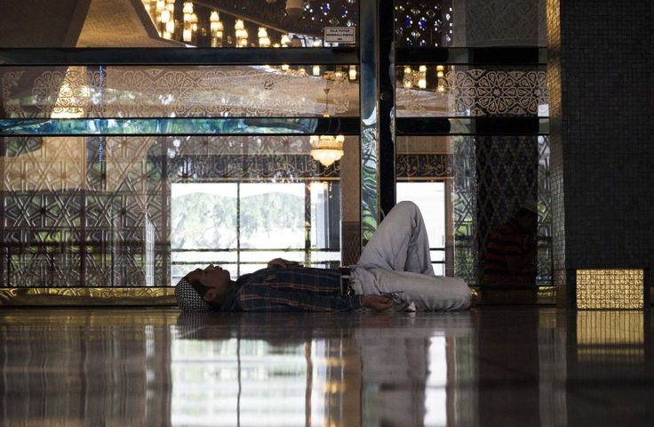 A man take a nap in mosque during the day of Ramadan .