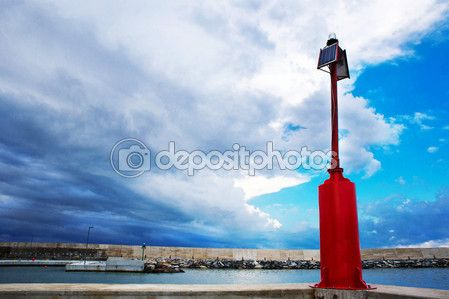 Faro rosso con le nubi tempestose in background — Immagine Stock #79214450