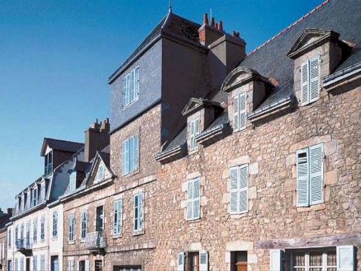 Maisons de négociants à Port-Louis. L'ensemble des trois grandes maisons de négociants armateurs résume l'évolution stylistique de Port-Louis sur 2 siècles. Le numéro 37, de 1703, représente l'époque Louis XIV : opulence majestueuse, corniche et lucarnes de granit. Le numéro 35, de 1779, est élégant avec un fronton percé d'un oculus ovale, des lucarnes en charpente, un balcon de fer forgé. L'enduit de chaux rehaussait les encadrements et bandeaux en granit taillé. Au numéro 33, de 1872, un…