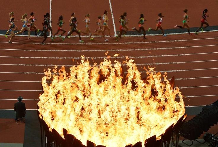 Agosto 3 de 2012 - Atletas corren pasando la antorcha olímpica mientras compiten en la final femenina de 10.000 metros. (AFP/VANGUARDIA LIBERAL)
