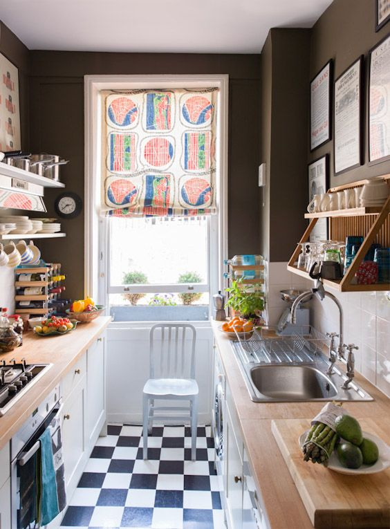 colourful patterned window shade + open shelving + chocolate brown walls + classic white tile and cabinets + butcherblock counters + checkered floor in galley kitchen by Ben Pentreath Ltd