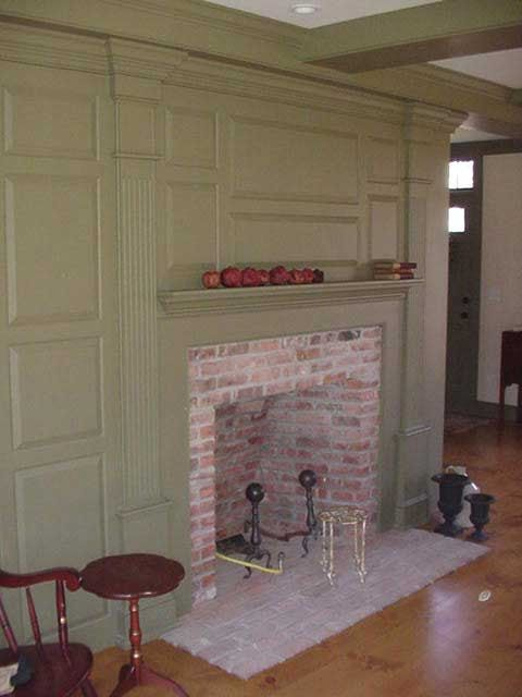 FARMHOUSE  INTERIOR  raised panel walls simple molding and brick fireplace enhance this