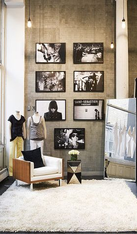 The black and white photos mixed with the soft texture of the rug, chair and cushion gives this store a very glamourous look.