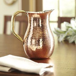 An elegant way to dispense water at the table, this hammered-copper pitcher boasts a cast-brass ice guard to prevent spills as well as a substantial brass handle. Lined with stainless steel and lacquered to preserve its finish. Available in 45 and 80 ounce capacity.