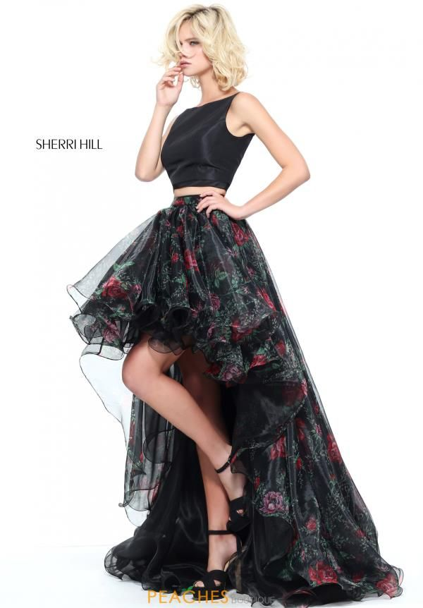 Look fun and flirty in this fashion forward two piece Sherri Hill prom dress 51098. Featuring a fitted solid crop top with a sophisticated high neckline and thin straps that lead to a simple open back. Showcasing an A-line skirt made in a rich organza fabric with a stunning floral print and a chic high low hem. Shop for more high low dresses at Peaches Boutique in Chicago.