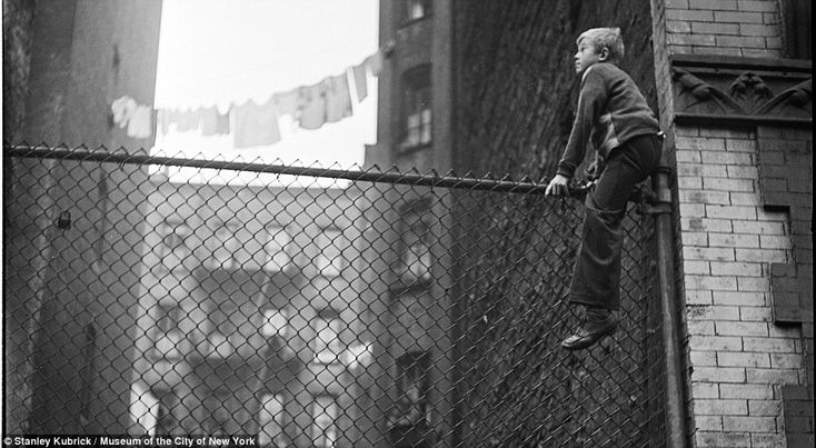 Hard knocks life: A boy climbs a high fence as washing hangs from building to building. By Stanley Kubrick