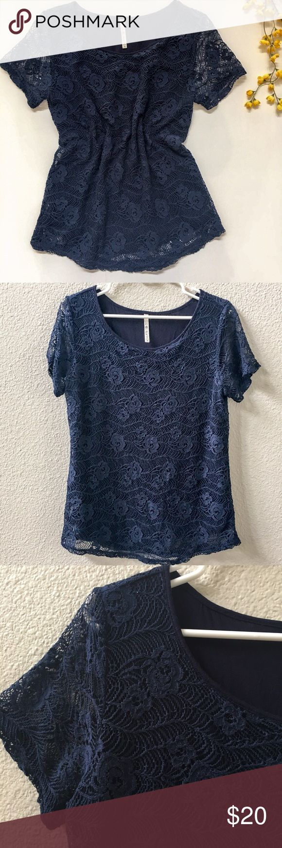 Navy short sleeve top with lace overlay Navy blue short sleeve top with lace overlay. Lining is sleeveless so lace shows on arms and hem line. Pretty floral pattern. Great dressy tee. Good used condition. Some pilling on inside of the top but it doesn't show and the lace looks great! Leo & Nicole Tops