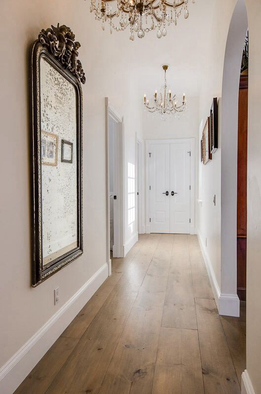 Love the contrast of wide planked floors in the hallway and crystal chandeliers