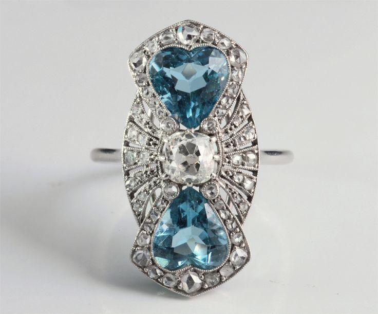 """Bague Art Déco, entièrement en platine, de forme marquise, d'un dessin très original et très élégant, associant un diamant taille cousin au centre (4,7 x 4,7 mms, environ 0,55 carat) et deux aigues-marines en forme de Coeur, d'un bleu très soutenu. Des petits diamants taillés en """"roses"""" habillent le plateau de la bague. Travail français, vers 1930."""