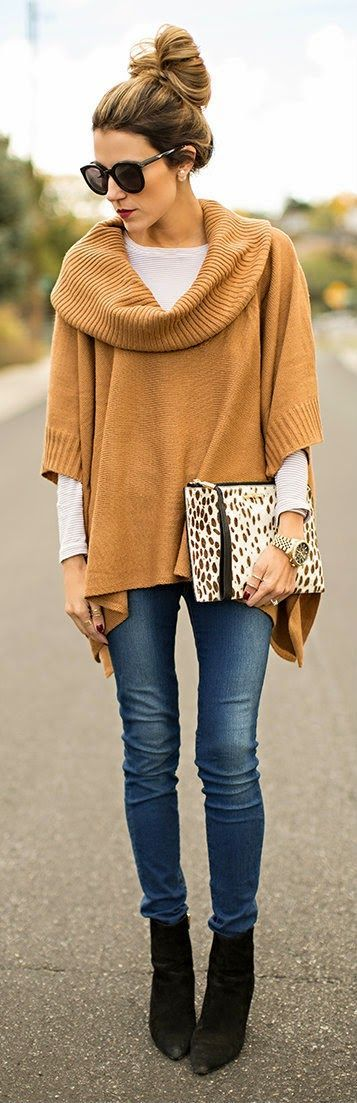 Oversized sweater layered over a tee with casual clutch and booties: