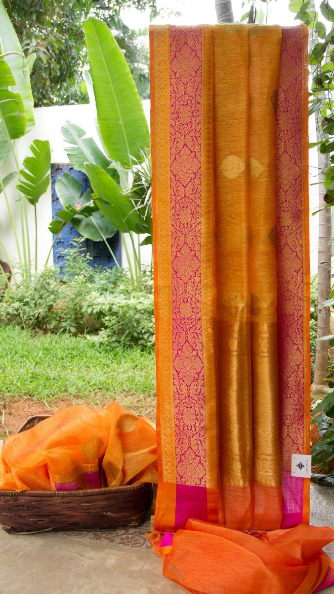 This Benares linen is in orange with gold zari bhuttas throughout. The border is in magenta and orange with gold zari weave, while the pallu is in fire orange with elaborate gold zari work making i...