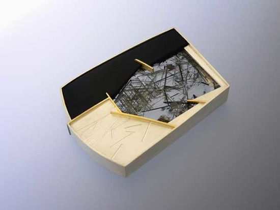 """""""Saganitic"""" Brooch by artist Eleanor Moty, featuring saganitic rutilated quartz and black paper micarta, set in sterling silver and 18K gold."""