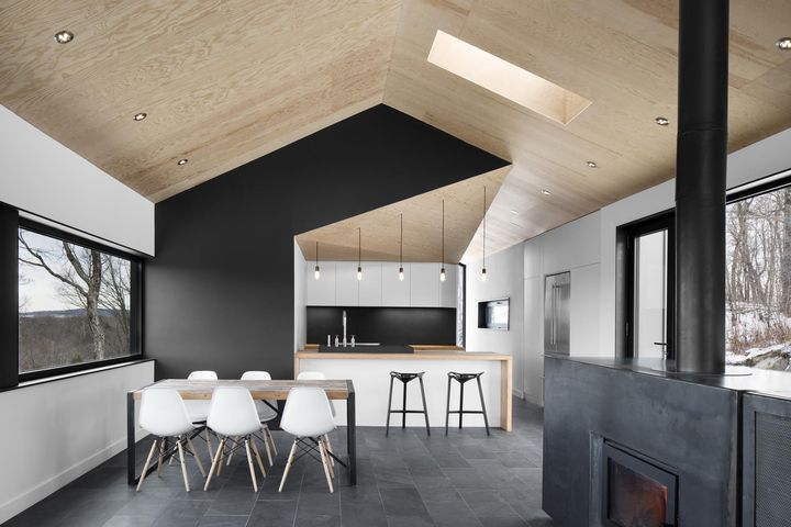 The architects stuck to a gray-scale color palette, installing slate tile floors that softly contrast with the white walls and Eames dining chairs. Photo by Adrien Williams.