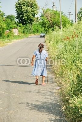 Village of Peris, judetul Ilfov - old woman walking on strada Orhideelor