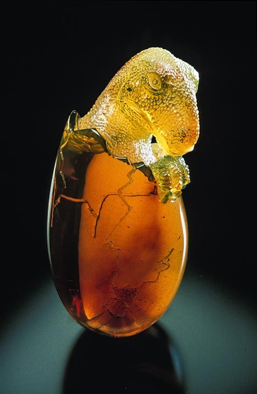 """Dinosaur Carving in Amber - The Greeks called amber """"elektron,"""" or """"made by the sun."""" Homer praised its bright glow. The Egyptians buried it in tombs for the afterlife. Today's scientists value amber too: it provides a three-dimensional window into prehistoric ecosystems through the myriad animal and plant inclusions it contains."""