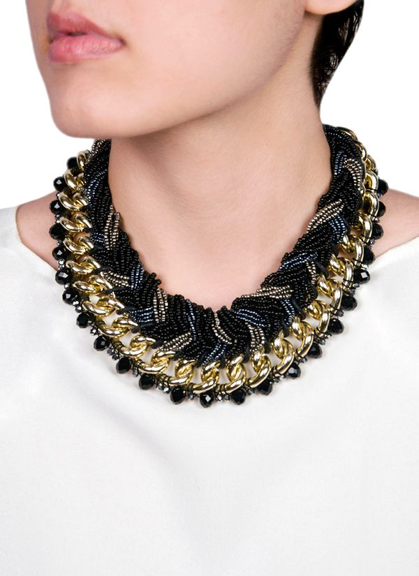 Make a bold statement with this grey and black beaded collar necklace from Rhea. Detailed with intricate beading and sparkling crystals, this necklace offers a chunky look with woven layers of beads in different shades of black and grey and sturdy gold-tone chain link accents that add an ultra-modern touch.