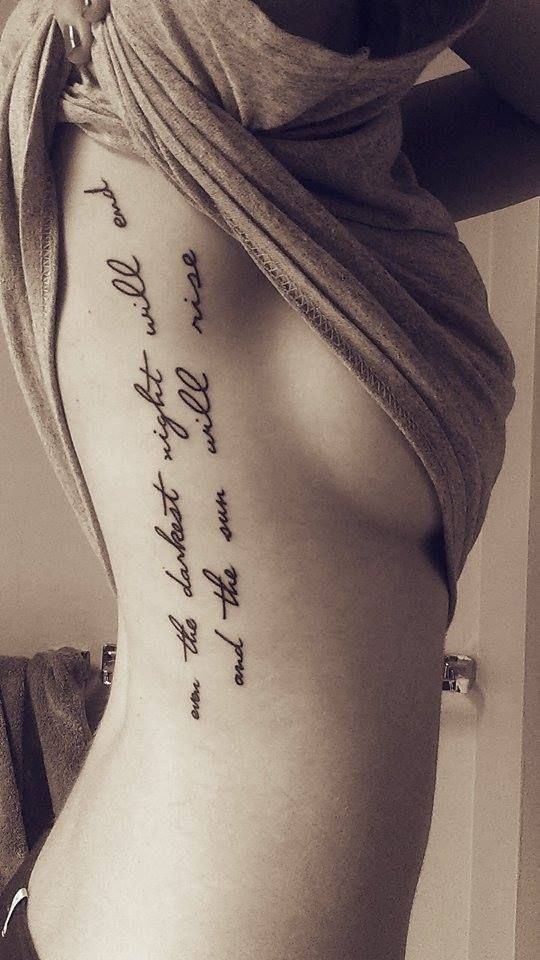 Script Les Mis tattoo on back/ribs.