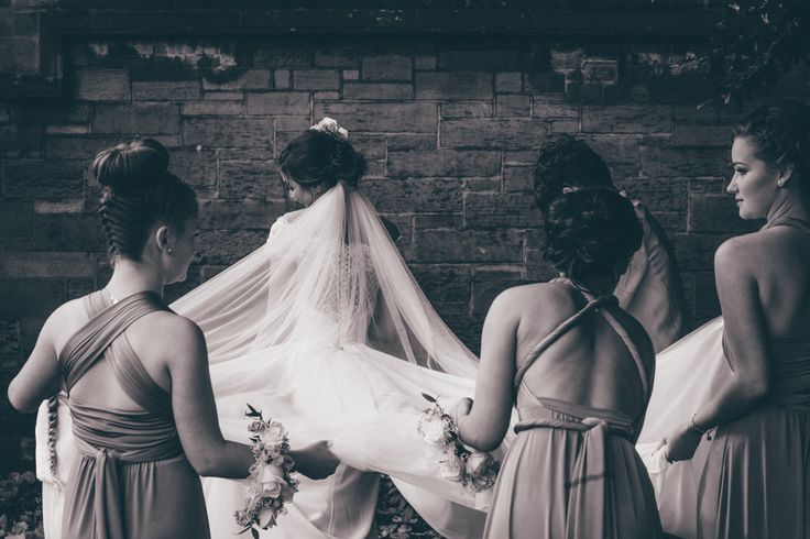 Bridesmaids in multiway gowns, helping their bride with her veil. Cheshire.