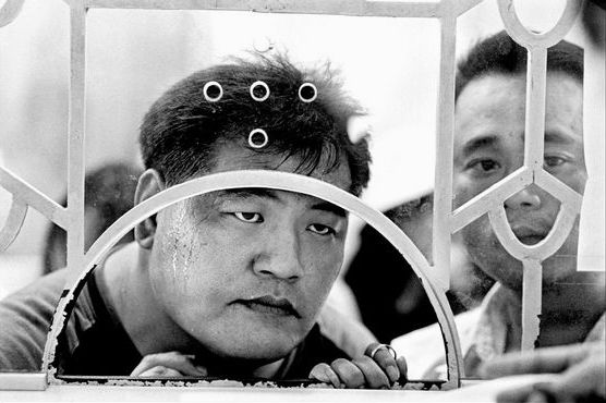 by Chien-Chi Chang, Couples present proof of identity and marriage so that the women can get visas to Taiwan, Ho Chi Minh City, 2003